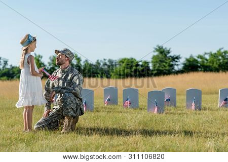 military man in cap sitting near child in straw hat and headstones in graveyard poster