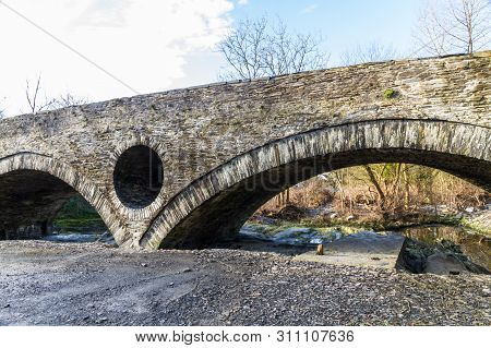 Old Bridge Arch Over River With Low Level.