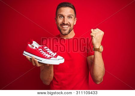 Young man holding casual sneakers shoes over red isolated background screaming proud and celebrating victory and success very excited, cheering emotion
