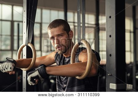 Tired handsome strong man holding on to gymnastic rings at gym. Closeup portrait of fitness man taking a break after intense workout at gym. Young man relaxing with arms in gymnastic rings.