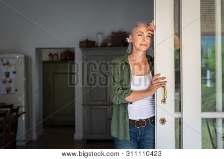 Thoughtful senior woman standing at home entrance leaning against door. Mature woman waiting husband at doorway and looking away. Lady in casual clothing standing at door and thinking.