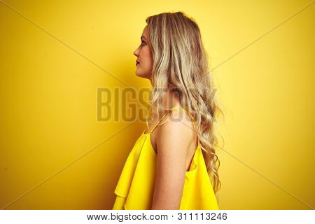 Young attactive woman wearing t-shirt standing over yellow isolated background looking to side, relax profile pose with natural face with confident smile.