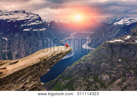 Norway, A woman sits on the mountain's cliff edge of Trolltunga throning over Ringedalsvatnet  watching the sunset and snowy Norwegian mountains near Odda, Rogaland, Norway.