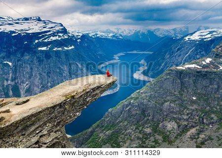 Norway, A woman sits on the mountain's cliff edge of Trolltunga throning over Ringedalsvatnet watching the  the snowy Norwegian mountains near Odda, Rogaland, Norway.