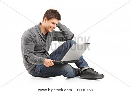 A smiling male working on a laptop isolated on white background