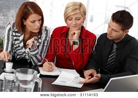 Businessteam at meeting, businesspeople reviewing documents, taking notes, working together.