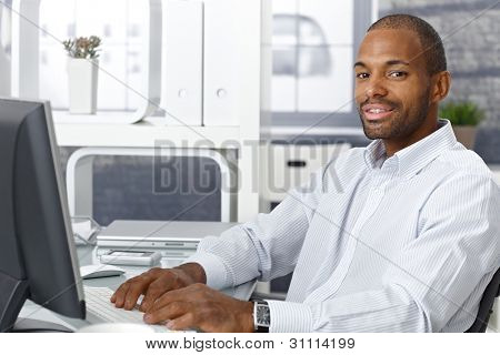Businessman working on computer at office desk, looking at camera, smiling.