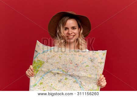 Happy Blond Girl With Curly Hair In A White T-shirt And A Sundown Hat Looks At The Map Looking For I
