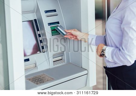 Business Woman Using Atm. Person Using Credit Card To Withdrawing Money From Atm Machine.