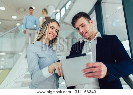 Beautiful Business Woman And Man Holding A Tablet In Hands And Smiling At The Camera. In The Backgro