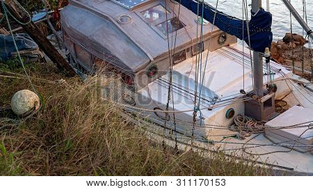 A Decrepit Damaged Old Wooden Boat Abandoned In A State Of Disrepair Run Ashore On A Mangrove River