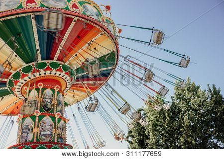 Carousel With Chains In An Amusement Park On A Summer Sunny Day