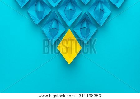 Yellow Paper Ship Ahead Of Blue Ones Leadership Concept. Metaphorical Conceptual Leadership Image Ov