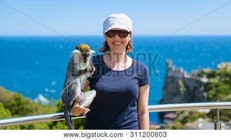 Young Woman Posing With A Monkey On The Black Sea Coast Of Crimea, Russia. Female Tourist Relaxing I