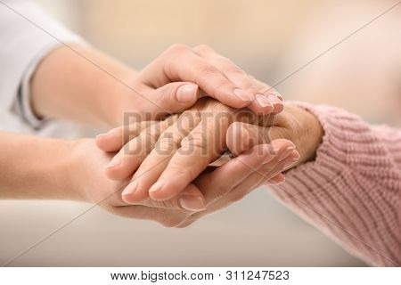 Nurse Holding Hands Of Elderly Woman Against Blurred Background, Closeup. Assisting Senior Generatio