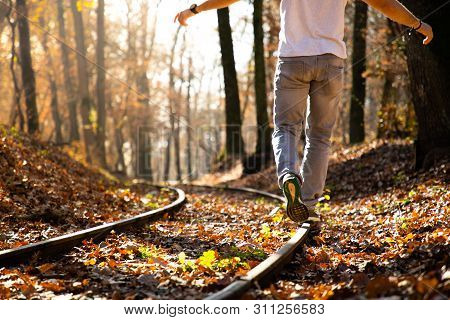 Man Walking On Train Rails On Fall With Leaves On The Ground During Sunset
