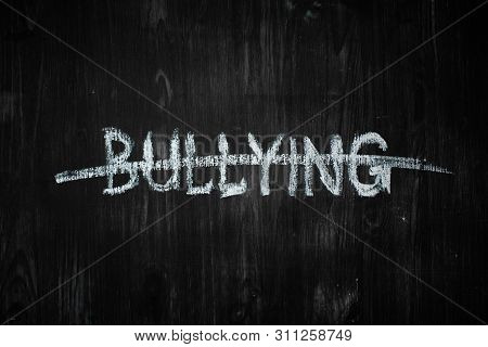 Bullying Word Crossed Out On Black Wood Background. Sign, Concept Of Dealing With Behaviour Social I