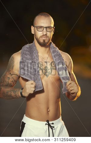 Muscle Tattooed Man Execising On Summer City Way