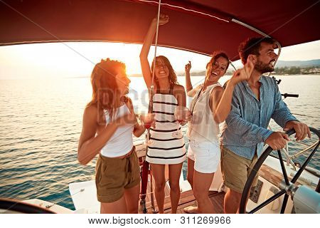 young people on vacation travel on boat together and have fun at sunset
