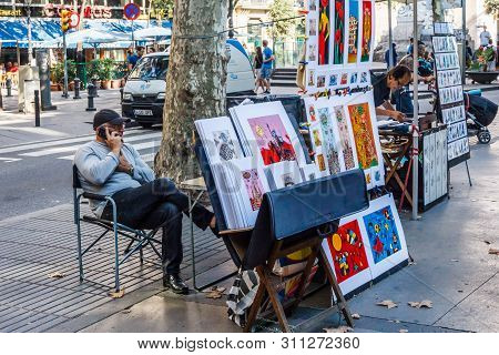 Barcelona, Spain-september 5th 2015: Man On Phone Selling Paintings On One Of The Ramblas. The Rambl