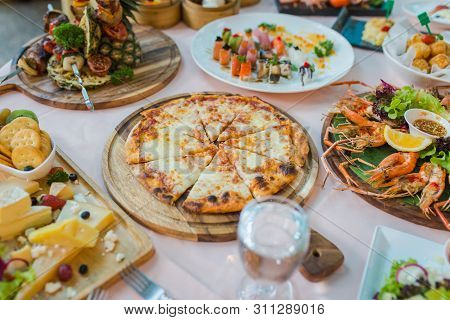 Picture Of Dinner Table With Variety Food Set, Pizza, Seafood And Sushi