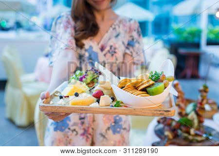 Woman Present The Plate Of Healthy Balanced Breakfast Of Cheese, Biscuits And Fresh Fruit.