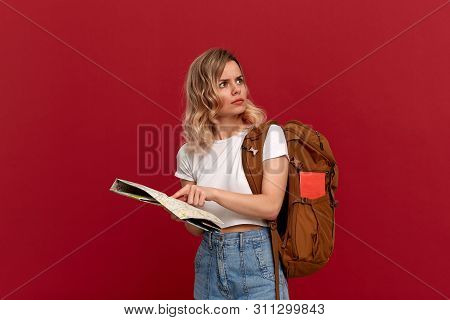 Confused Blond Girl With Curly Hair In A White T-shirt Trying To Find Itinerary With The Map Holding