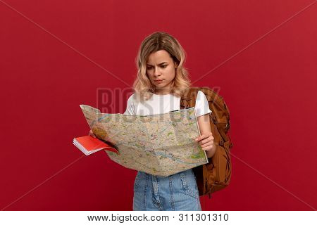 Shocked Blond Girl With Curly Hair In A White T-shirt Looks At The Map Trying To Find Itinerary Hold