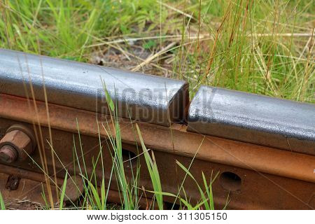 The Junction Of Two Old Rail Rails On The Background Of Grass. The Concept Of Disagreement, Discrepa
