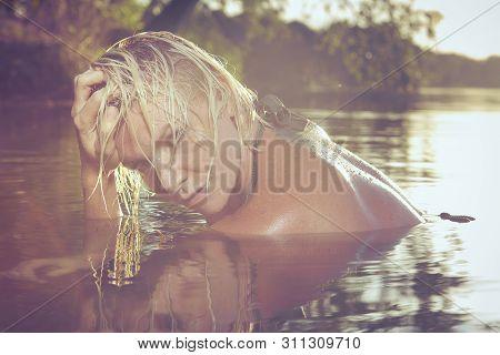 Pretty Blonde Lady In Swimsuit Relaxing In Lake