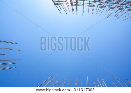 Reinforced Steel Bars Against The Blue Sky. Metal Base Of Reinforced Concrete Walls. Part Of The Str