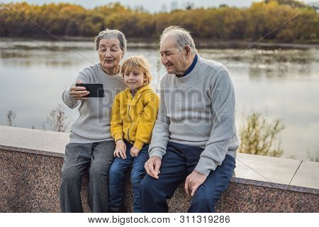 Senior Couple With Great-grandson Take A Selfie In The Autumn Park. Great-grandmother, Great-grandfa