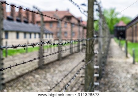 Barbed Wire Fence In Concentration Camp Auschwitz I At Oswiecim - Poland. Black And White Photo