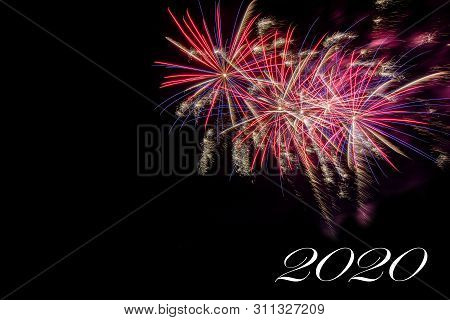 Bursting Fireworks Against Black Background Celebrating The Arrival Of 2020, The End Of A Decade