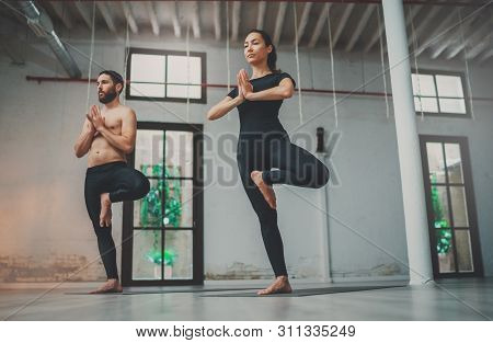Yoga Practice Exercise Class Concept. Young Woman And Man Practicing Yoga Indoors. Two Sporty People
