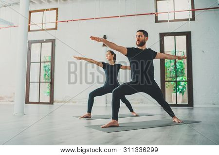 Young Sportive Man And Woman Are Practicing Yoga Exercises In The Studio. Couple Of Young Sporty Peo