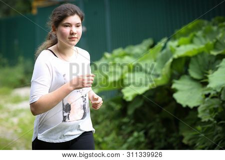 Teenager Girl With Long Dark Hair Jogging On Coutry Summer Road Close Up Photo