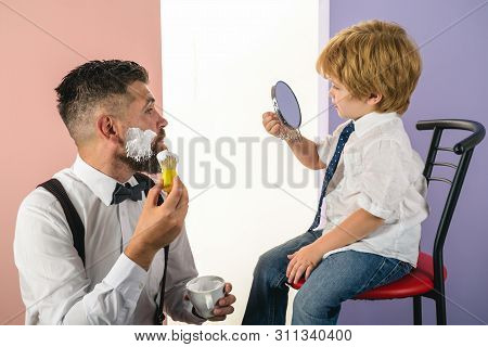 Barbershop. Trendy And Stylish Father And Son. Barber Shaving A Bearded Man In A Barber Shop. Barber