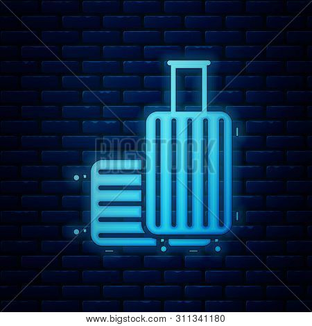 Glowing Neon Suitcase For Travel Icon Isolated On Brick Wall Background. Traveling Baggage Sign. Tra