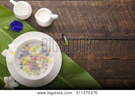 Thai Sweets And Colorful Ball Flour In A White Cup On A Banana Leaf, Coconut On An Old Wooden Table