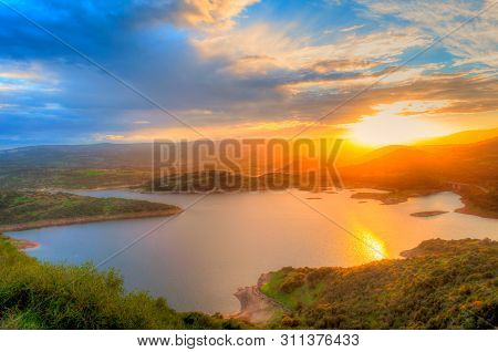 Sunset On The Lake With Sun Between The Mountains