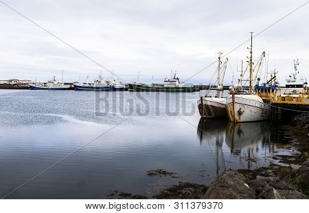 On The Photo You Can See A Commercial Fishing Port Where Several Trawlers Are Tied Up