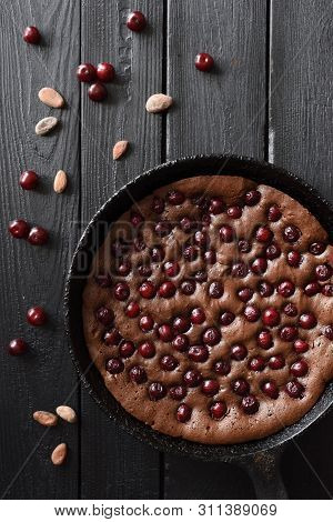 Homemade Dessert Flatlay. Yummy Chocolate Pie With Cherries And Cocoa Beans In Cast Iron Pan On Blac