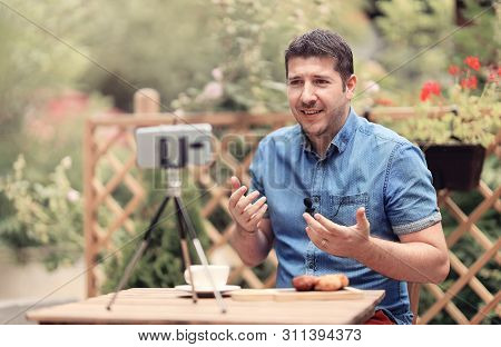 Young man speaks in front of phone camera with attached mic lavalier. Vlogger man sitting on a table and making a vlog episode. Man explaining and gesturing in front of a camera. Blogging (vlogging) and technology concept