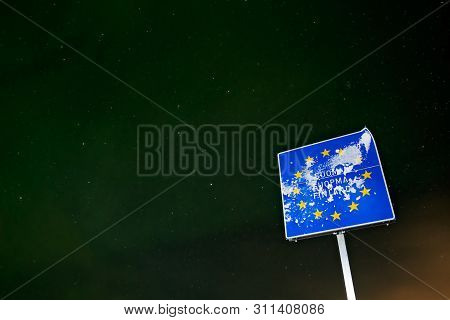 Covered In Snow Blue Sign With European Union Yellow Stars Marking Border Between Norway And Finland
