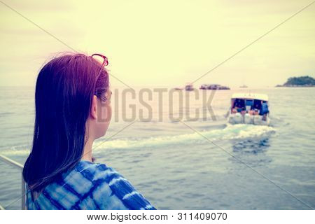Back Of Asian Woman Looking At The Speed Boat That Sailed Away From Her, With A Lonely, Solitary, Sa