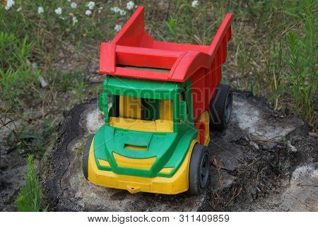 One Big Colored Toy Dump Truck Stands On A Stump In The Green Grass