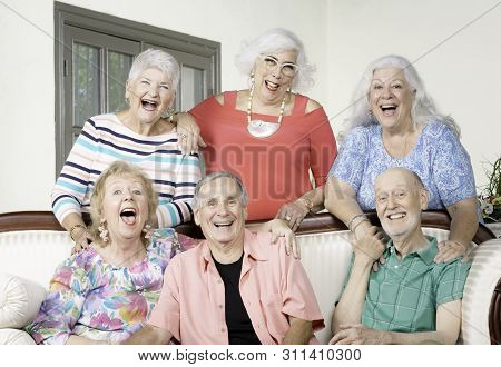 Six Senior Friends Laughing Out Loud Around An Antique Couch