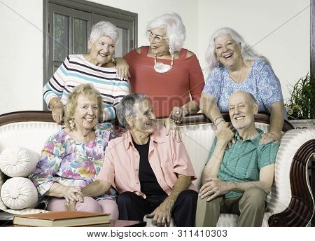 Six Senior Friends Laughing Around An Antique Couch