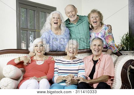 Six Cheerful Senior Friends Laughing Around An Antique Couch